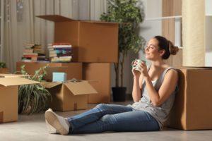 Frau sitzt entspannt vor Umzugskartons und lächelt